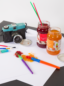 A camera looks on to a canvas covered in jam splatters, with brushes and jam jars